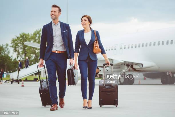 Young business people walking in front of airplane