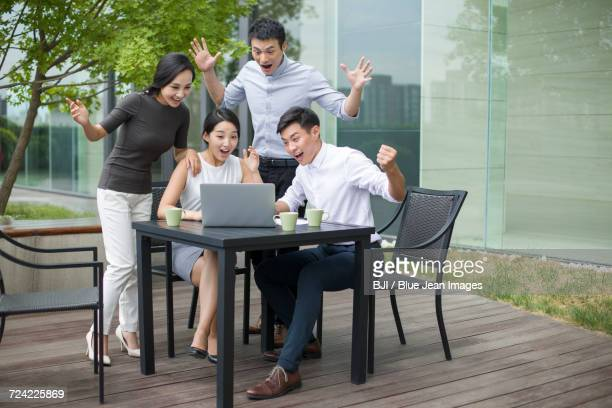 Young business person cheering outdoors
