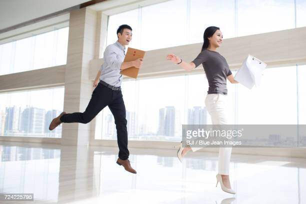 Young business person jumping in office building