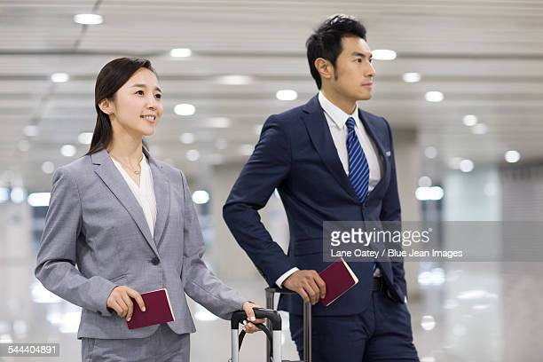 Young business person with suitcases in airport