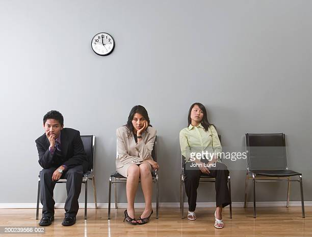 Young business professionals, sitting in waiting room, looking bored