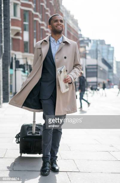 Young business traveler carrying his bag on the street
