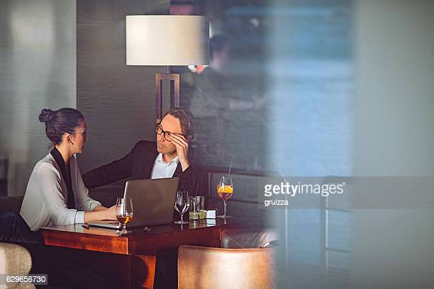 Young business woman and man having conversation at a restaurant
