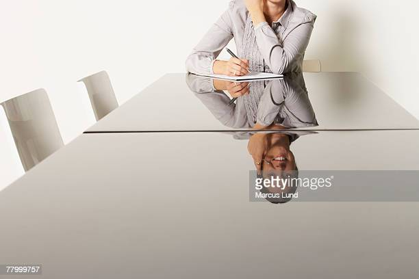 Young business woman at desk with reflections.