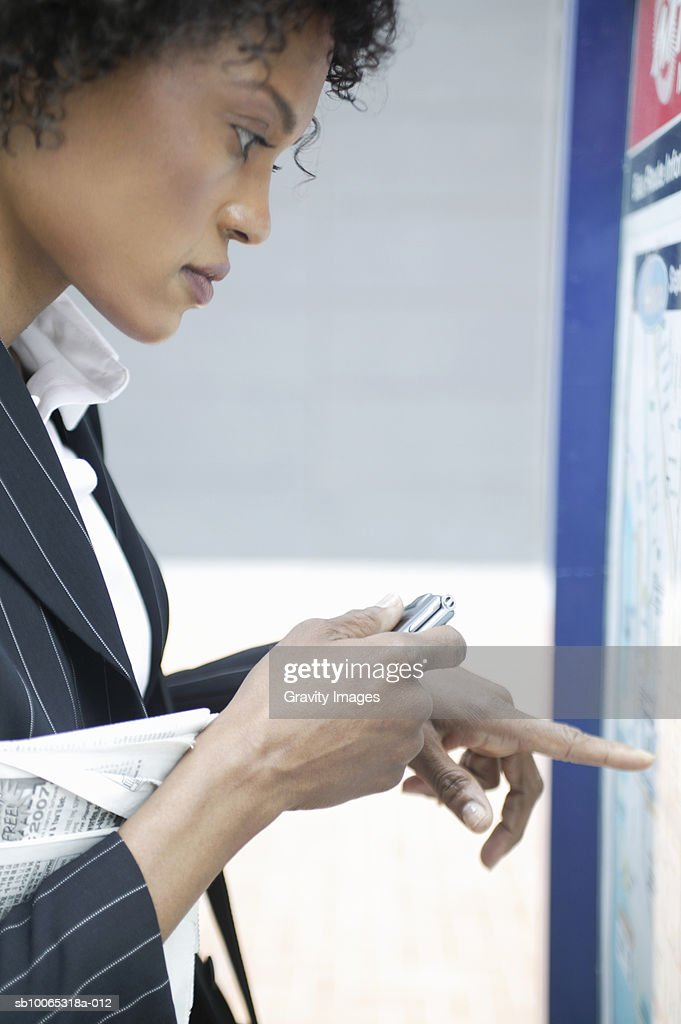 Young business woman checking timetable : Foto stock