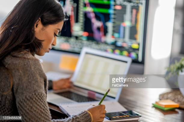 young business woman day trading from her dining room table - fatcamera stock pictures, royalty-free photos & images