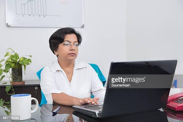 Young Business Frau tief engrossed, während Sie an Ihrem Laptop arbeiten.