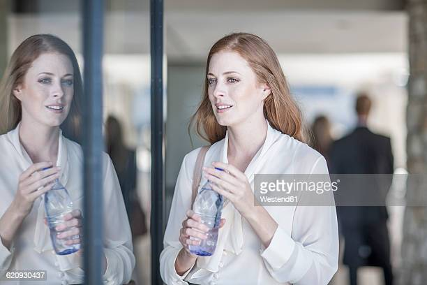 Young business woman drinking water