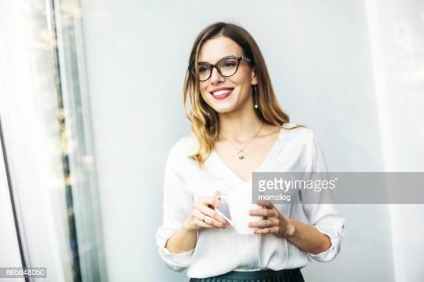junge geschäftsfrau, die ihren ersten morgenkaffee genießen - wegsehen stock-fotos und bilder