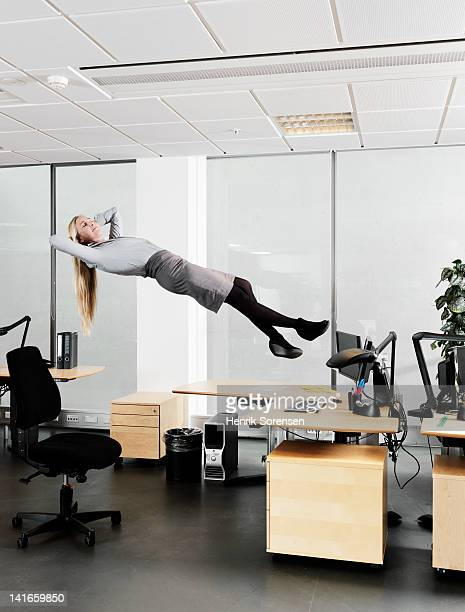 young Business woman floating above the desk