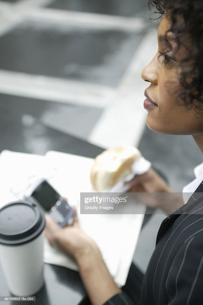 Young business woman having lunch and text messaging : Foto stock