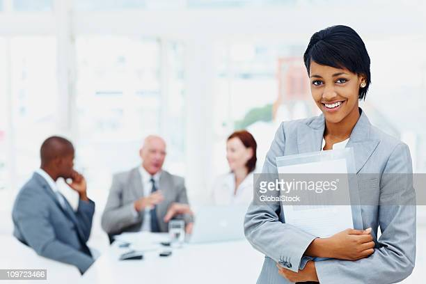 Young business woman holding folder and her team in background