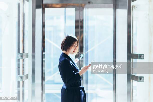 Young business woman holding smartphone and waiting for lift