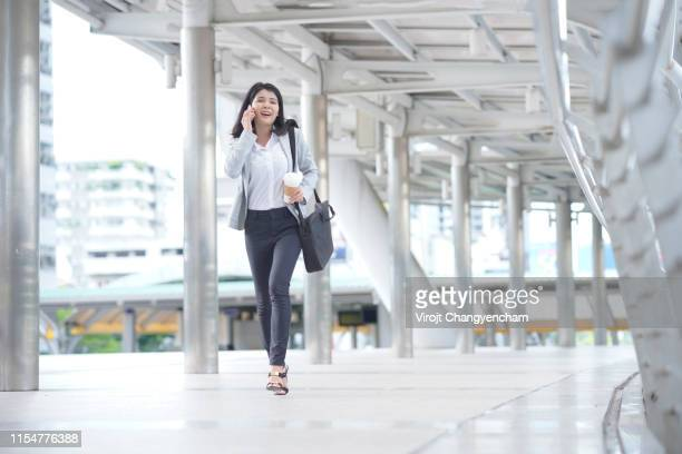 young business woman in the rush hour walking in the street. - 歩行者 ストックフォトと画像