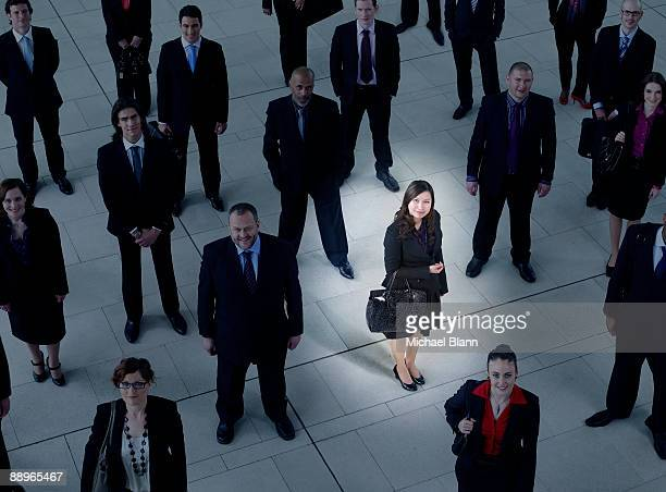 young business woman in the spotlight in a crowd - standing out from the crowd stock pictures, royalty-free photos & images