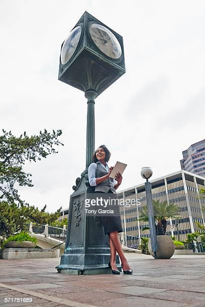 young business woman leaning against clock using digital tablet, looking away - ver a hora imagens e fotografias de stock