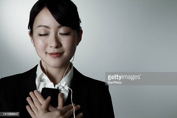 young business woman listening to music - 目を閉じた ストックフォトと画像