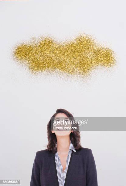 Young business woman looking at golden cloud