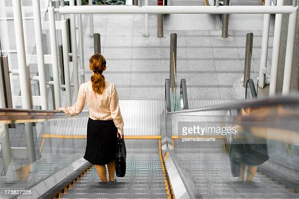 Young business woman on stairs (leaving office)