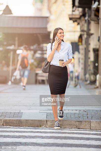 Young business woman passing the street on the crosswalk