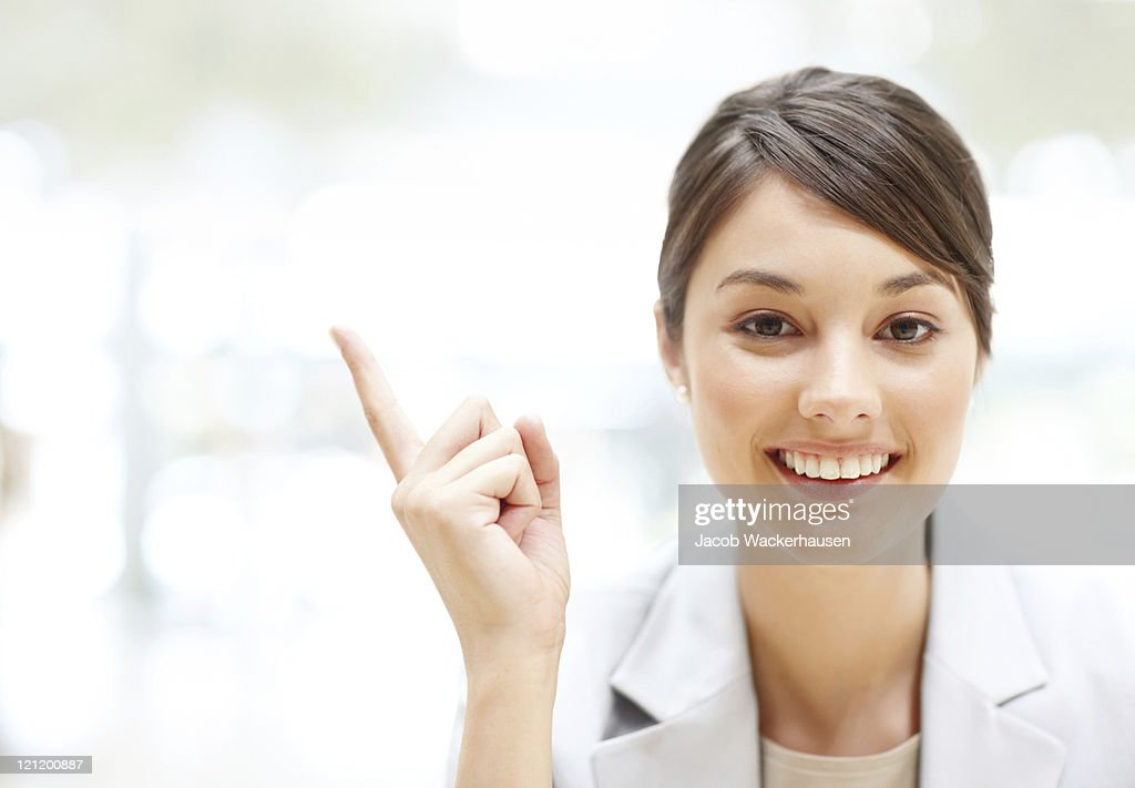 Young business woman pointing at copyspace : Stock Photo