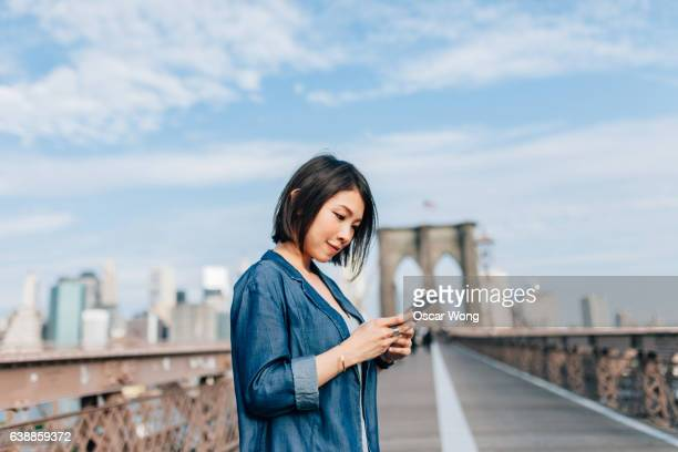Young business woman reading message on phone against cityscape
