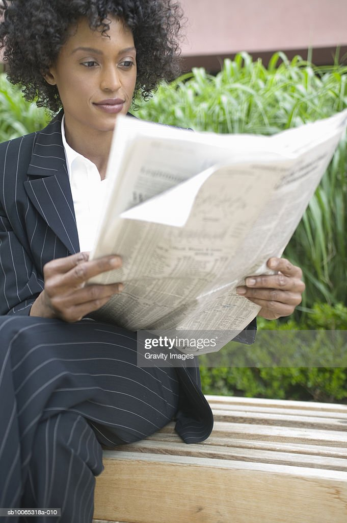 Young business woman reading newspaper on park bench : Foto stock