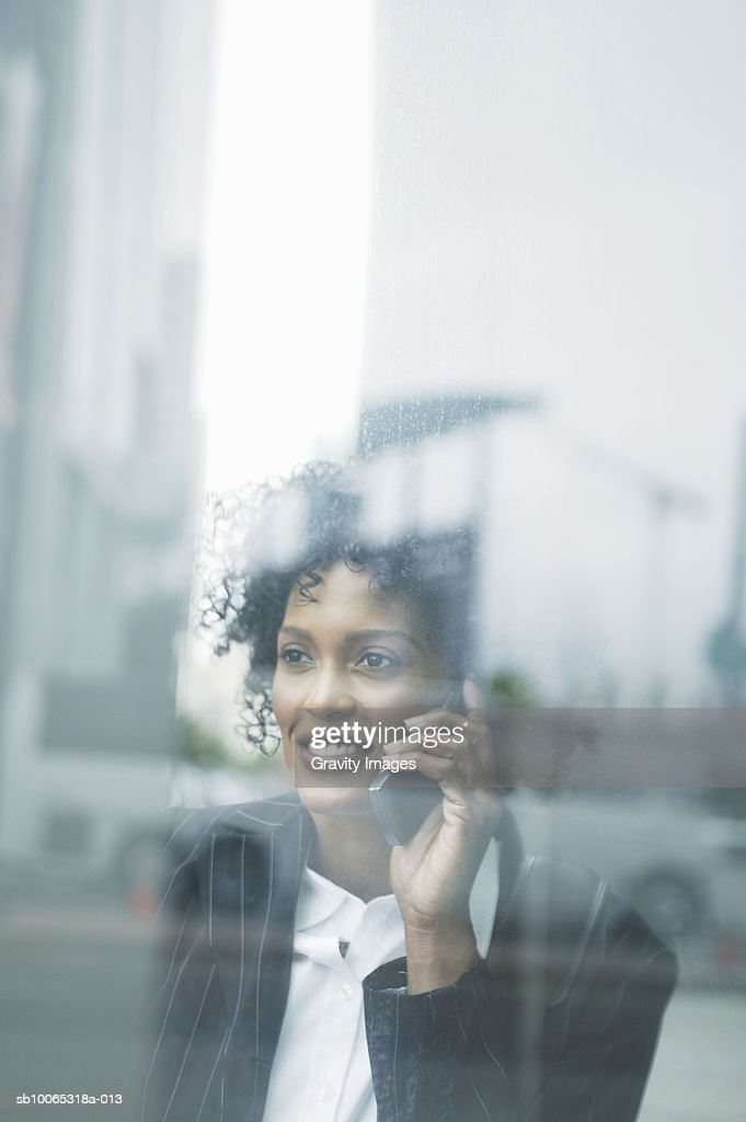 Young business woman seen through window, talking on phone : Foto stock