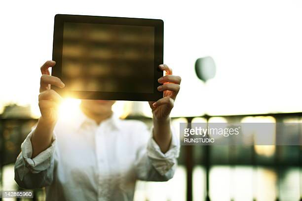 young business woman showing tablet pc - viso nascosto foto e immagini stock