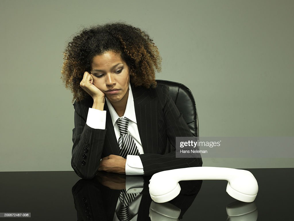 Young business woman sitting, oversized phone on desk : Stock-Foto