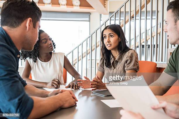 Young business woman talking in business meeting with colleagues