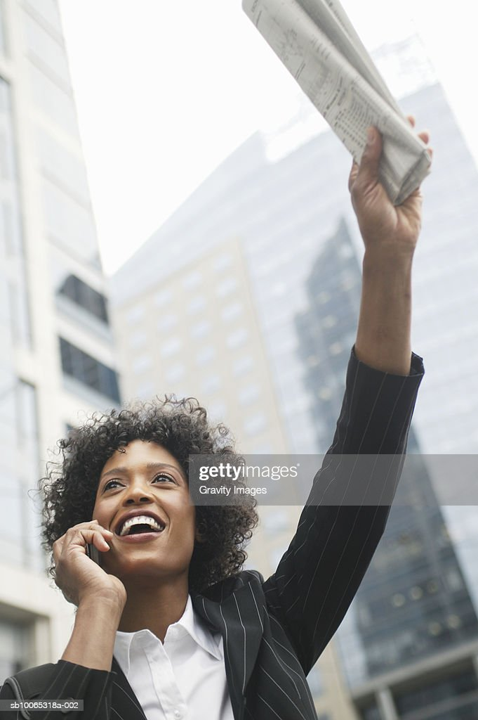 Young business woman talking on mobile whilst hailing taxi : Foto stock