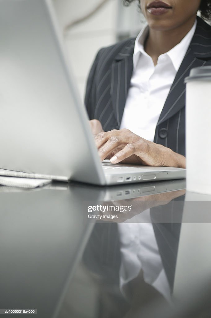 Young business woman typing on laptop, mid section : Foto stock
