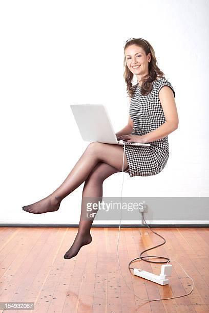 Jeune femme d'affaires à l'aide d'un ordinateur portable, l'air flottant