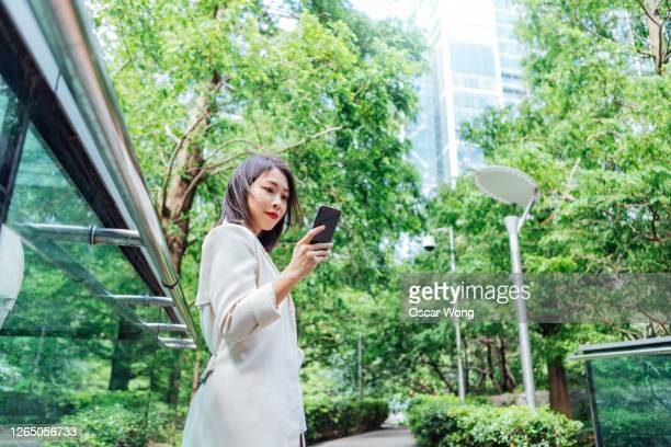 young business woman using smart phone at city park - sustainable lifestyle stock pictures, royalty-free photos & images