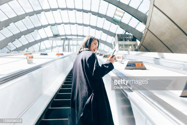 young business woman using smart phone, riding an escalator - station stock pictures, royalty-free photos & images