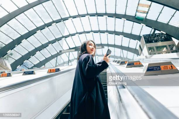 young business woman using smart phone, riding an escalator - facebook stock pictures, royalty-free photos & images