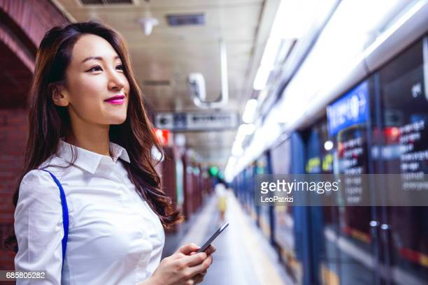 Young business woman waiting for the train in Seoul suwbay