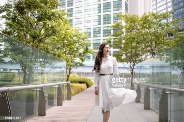 young business woman walking in urban city - wind blows up skirt stock pictures, royalty-free photos & images