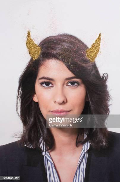 Young business woman wearing golden horns