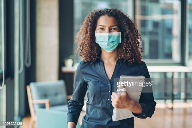 young business woman with face mask in the office - coronavirus mask stock pictures, royalty-free photos & images