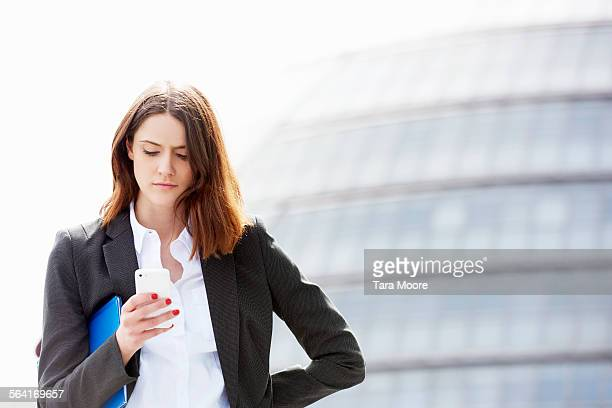 Young business woman with mobile outside offices