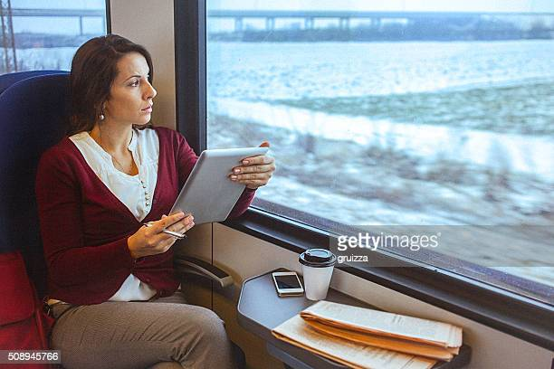 Young business woman working on tablet while commuting to work