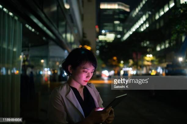 都会で夜外で働く若いビジネスウーマン - 仕事後 ストックフォトと画像