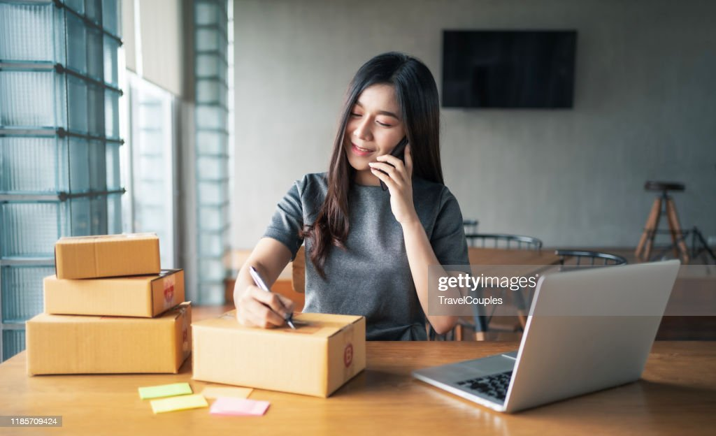 Young business woman working selling online. Entrepreneur owner using smartphone or laptop taking receive and checking online purchase shopping order to preparing pack product box. Packing goods for delivery to customer. E-commerce. Online Shopping : Stock Photo