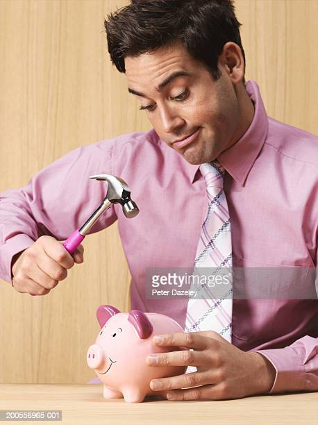 Young businessman about to smash piggy bank with hammer