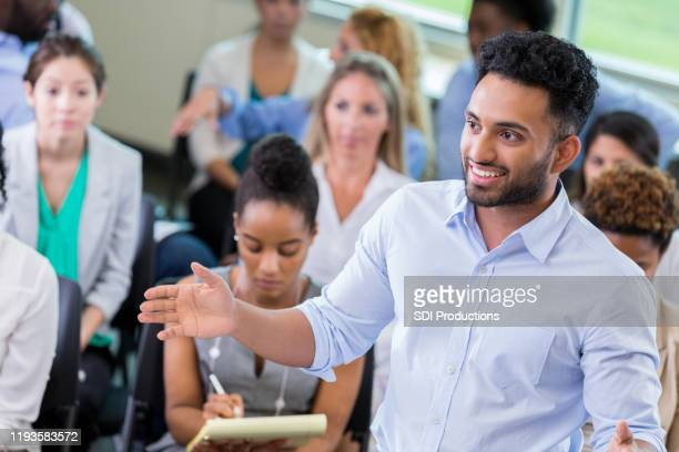 young businessman addresses colleagues during seminar - town hall stock pictures, royalty-free photos & images