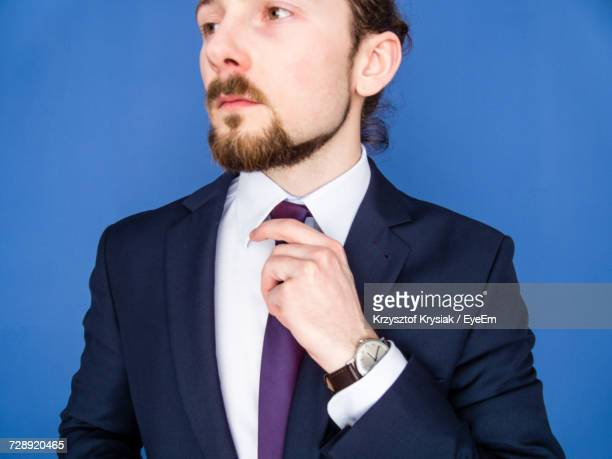 Young Businessman Adjusting Tie Against Blue Background