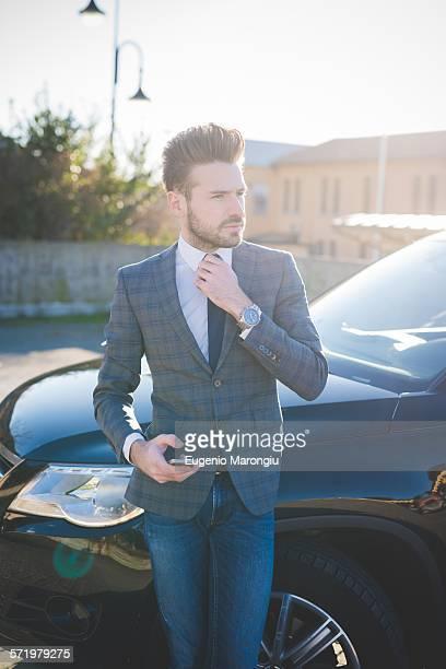 Young businessman adjusting tie in car park