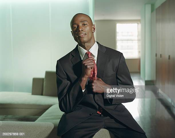Young businessman adjusting tie, smiling, portrait